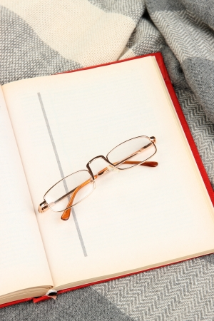 Composition with old book, eye glasses and plaid on wooden background photo