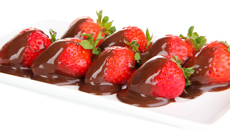 Strawberry dipped in chocolate fondue isolated on white photo