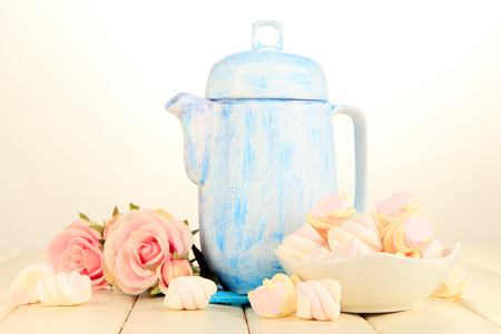 Antique white teapot on wooden table on white  photo