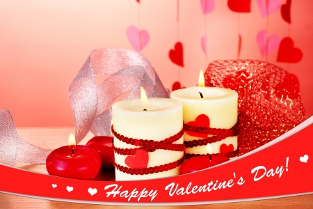 candles for Valentines Day on wooden table on red  photo