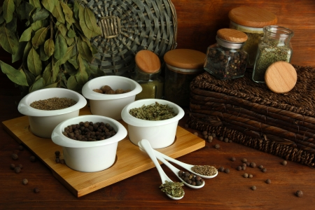 Assortment of spices in  white spoons and bowls, on wooden  photo