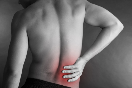 Young man with back pain on grey background Stock Photo