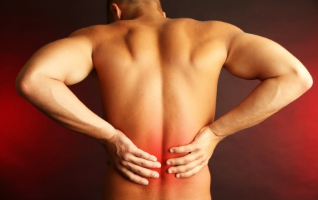 Young man with back pain on dark background photo
