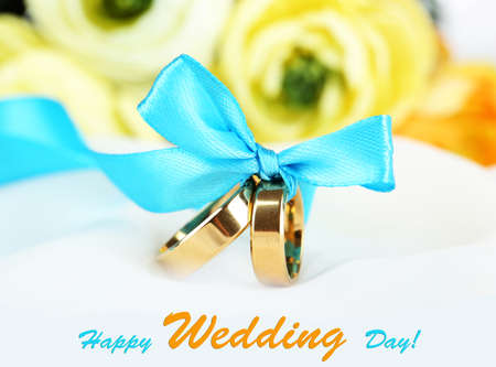 wedlock: Wedding rings tied with ribbon on white fabric background