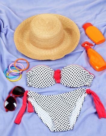 Swimsuit and beach items on purple background photo