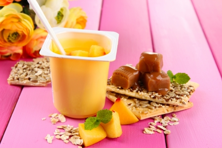 Tasty yogurt with pieces of fresh fruits, cookies and flakes,on color  wooden  photo