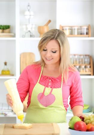 Happy smiling woman in kitchen preparing  sandwich  photo