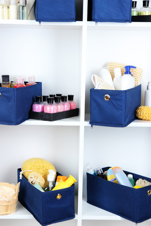 Blue textile boxes with cosmetic products for personal care in white shelves  photo