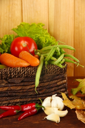 Different vegetables in basket with yellow leaves on table on wooden background photo