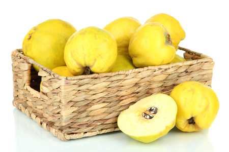 Sweet quinces in wicker basket isolated on white photo