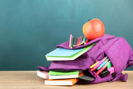 school desk: Purple backpack with school supplies on wooden table on green desk background