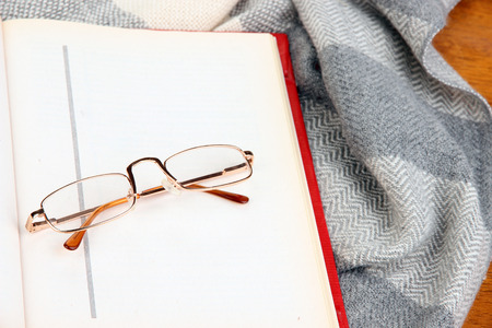 Composition with old book, eye glasses and plaid on wooden  photo