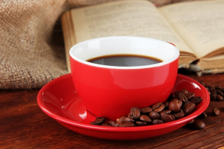 Cup of coffee with coffee beans and book on wooden table on sackcloth background Stock Photo - 23737312