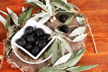 Olives in bowl with branch on sackcloth on wooden table Stock Photo - 23737316