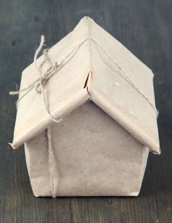 House wrapped in brown kraft paper, on wooden background photo