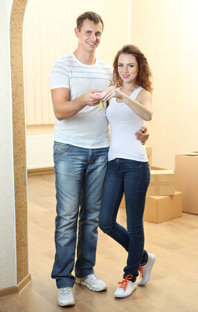 Young couple with keys to your new home on room background  photo