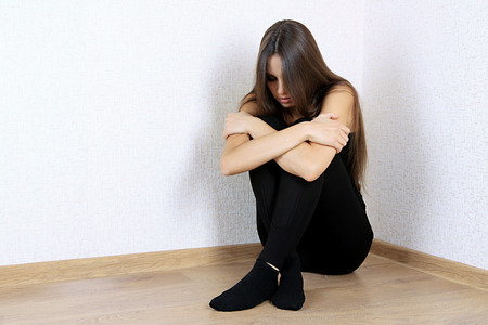 Lonely sad woman sitting on floor near wall Stock Photo - 24388896