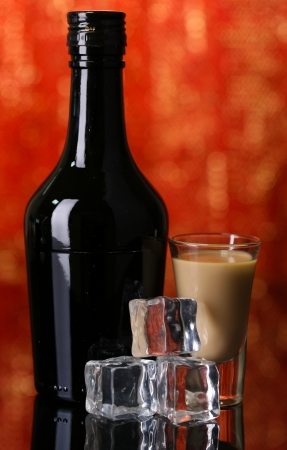 Baileys liqueur in bottle and glass on red background photo