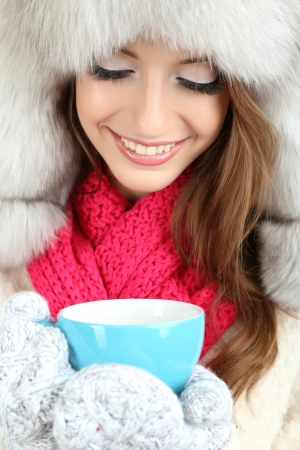 Beautiful girl in hat with cup close-up photo