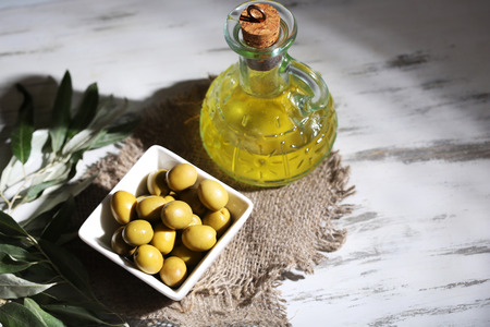 Olive oil and olives in bowl on sackcloth on wooden table Stock Photo - 23737550