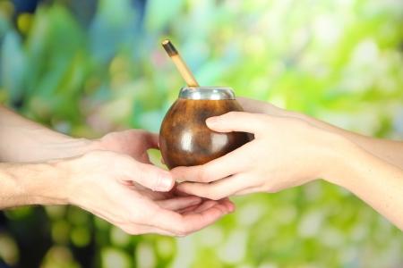 yerba mate: Manos de mujer dando calabaza y bombilla con yerba mate, en el fondo la naturaleza Foto de archivo