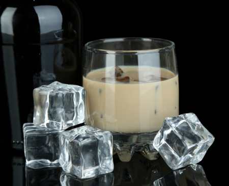Baileys liqueur in bottle and glass isolated on black photo