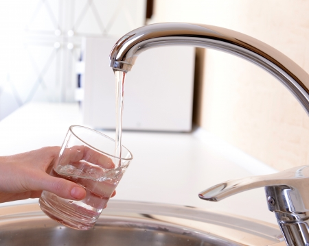 drinkable: Hand holding  glass of water poured from  kitchen faucet