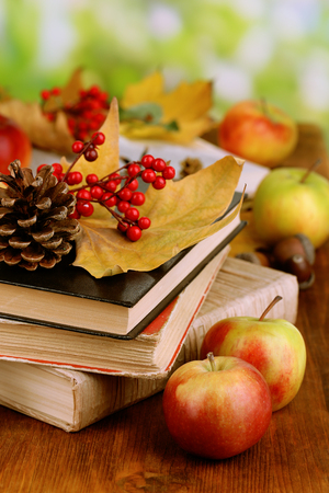 Books and autumn leaves on wooden table on natural background photo