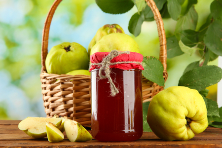 jar of jam and quinces with leaves in basket, on green background photo