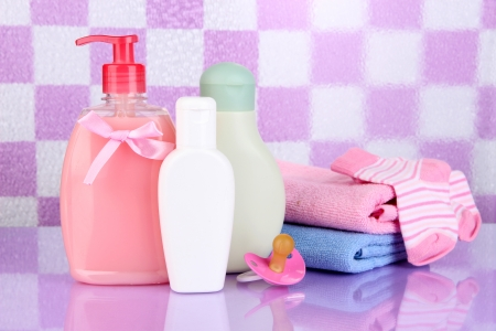 Baby Cosmetics And Towel In Bathroom On Pink Tile Wall Background ...