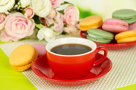 Coffee and macaroons on table on light background photo