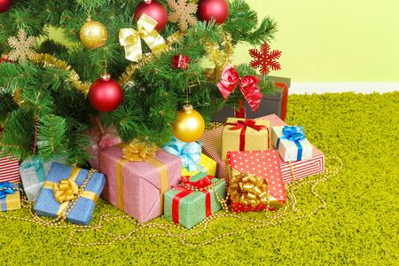 Decorated Christmas tree with gifts close-up photo