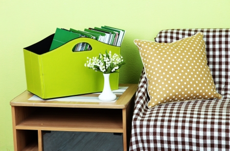 Magazines and folders in green box on bedside table in room Stock Photo - 23794644