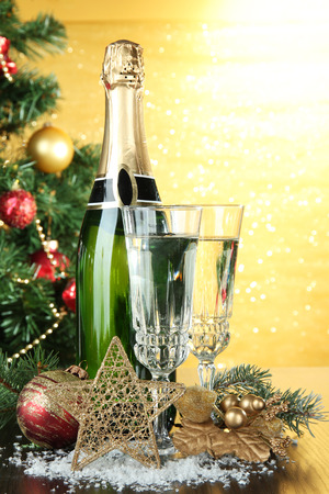 Composition with Christmas decorations and two champagne glasses, on bright background photo