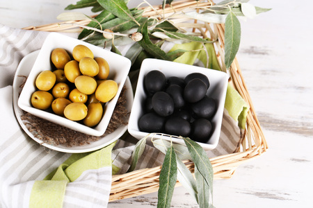 Olives in bowls with branch on napkin in basket on wooden table photo