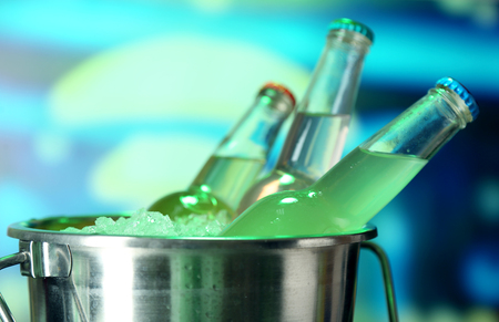 Bottled drinks in ice bucket on bright background photo