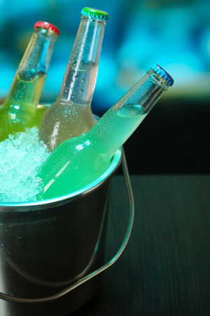 Bottled drinks in ice bucket on table on bright background photo