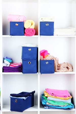 Blue textile boxes with towels and clothes in white shelves  photo