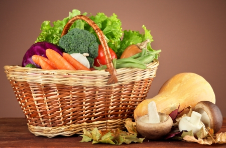 Different vegetables in basket with yellow leaves on table on brown background photo