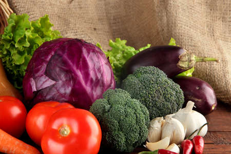 Composition of different vegetables on table on sackcloth background photo