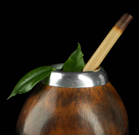 mate infusion: Calabash and bombilla with yerba mate isolated on black Stock Photo
