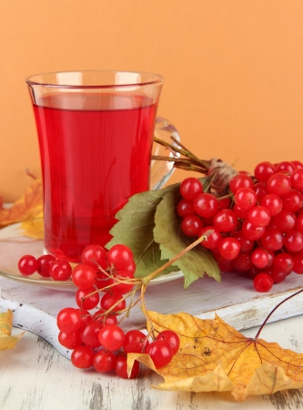 Red berries of viburnum and cup of tea on table on beige background photo