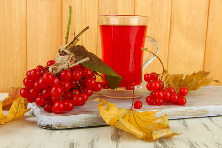 Red berries of viburnum and cup of tea on table on wooden background photo