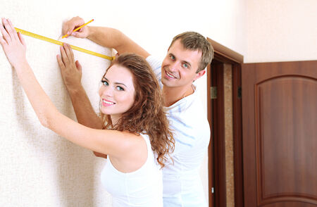 Young couple doing renovation in new house photo