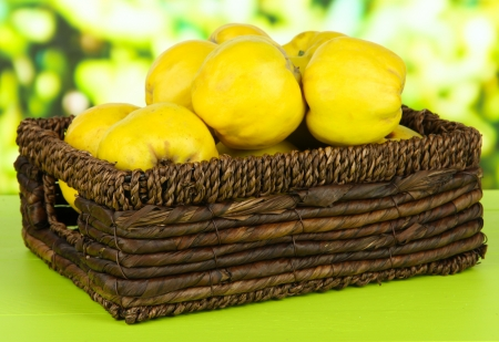 Sweet quinces in wicker basket on table on bright background photo