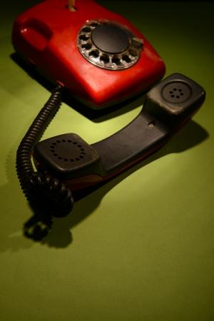 Red retro telephone on dark color background photo