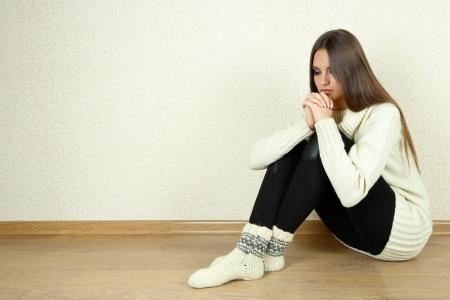 Sad woman sitting on floor near wall Stock Photo