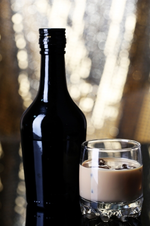 baileys: Baileys liqueur in bottle and glass on golden background Stock Photo