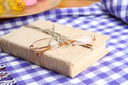 Composition with old book, eye glasses, and plaid on wooden background photo