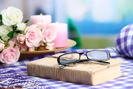 Composition with old book, eye glasses, candles, flowers and plaid on bright background photo